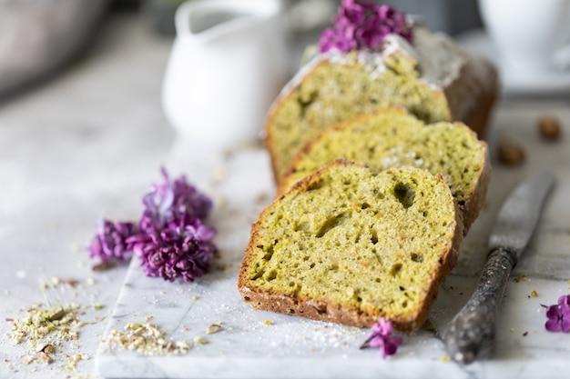 Gâteau aux pistaches et épinards avec une tasse de café avec un bouquet de lilas sur la table. copie espace