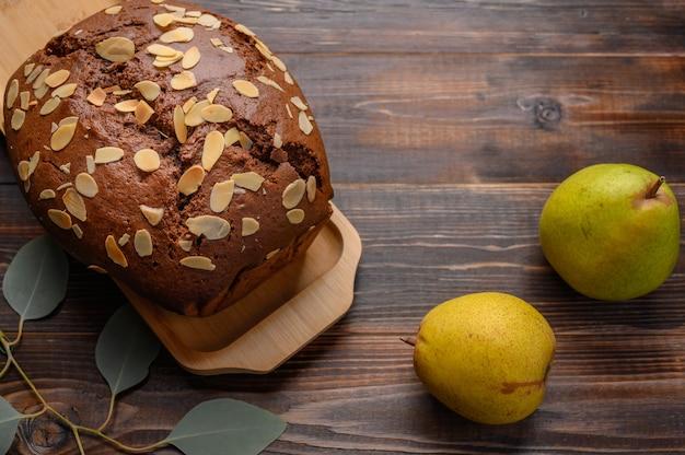 Gâteau aux poires au chocolat fait maison avec gingembre et cardamome sur un plateau en bois