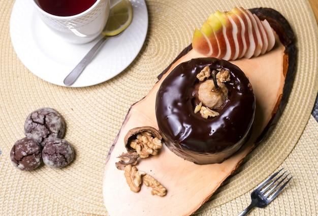 Gâteau aux poires sur la planche de bois avec chocolat aux noix et fruits frais vue de dessus
