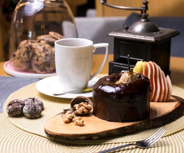 Gâteau aux poires sur la planche de bois avec chocolat aux noix et thé aux fruits frais vue latérale