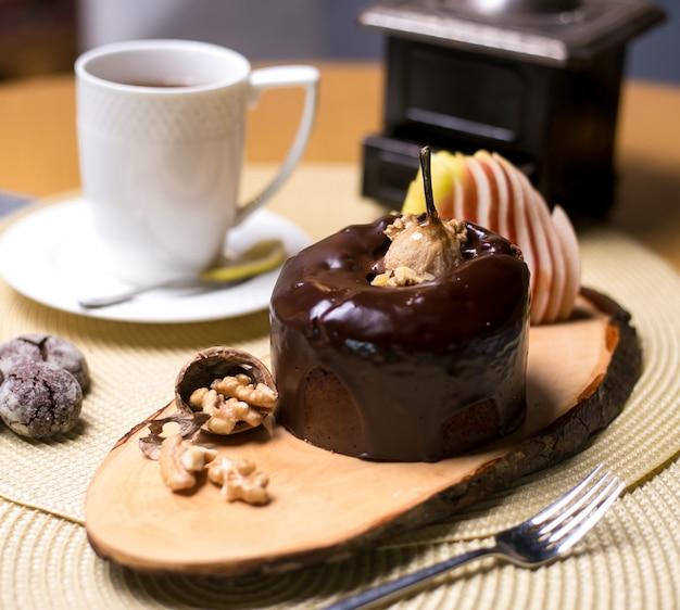 Gâteau aux poires sur la planche de bois avec du chocolat aux noix et des fruits frais vue latérale