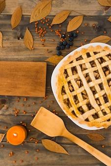 Gâteau aux pommes près d'une planche à découper entre le feuillage et les baies
