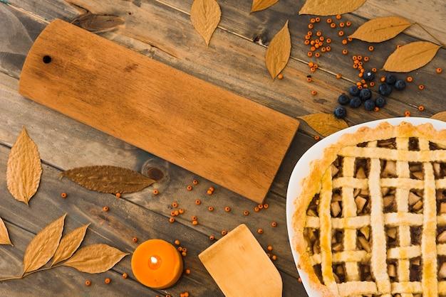 Gâteau aux pommes près d'une planche à découper entre les feuilles