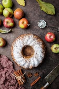 Gâteau aux pommes de style rustique saupoudré de sucre glace sur une vieille table en bois