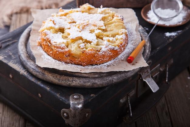 Gâteau aux pommes sur une valise vintage au sucre en poudre.