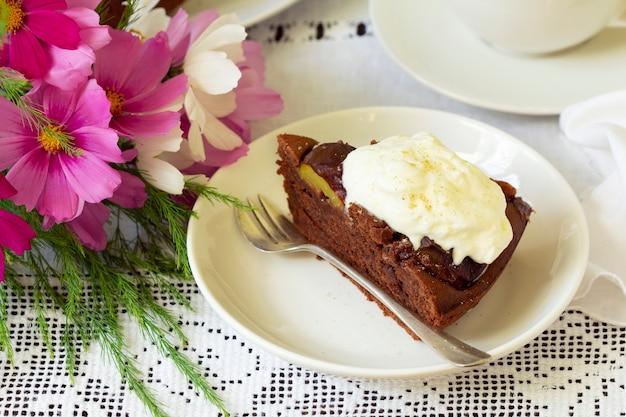 Gâteau aux prunes au chocolat avec crème fouettée, servi avec du cacao. style rustique.