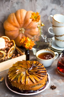 Gâteau aux prunes décoré avec des prunes tranchées parmi le décor d'automne