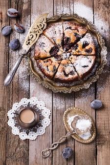 Gâteau aux prunes avec du sucre en poudre et une tasse de café