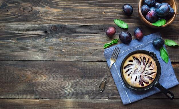 Gâteau aux prunes fait maison dans une poêle en fer sur fond de bois rustique. vue de dessus. copiez la zone de l'espace.