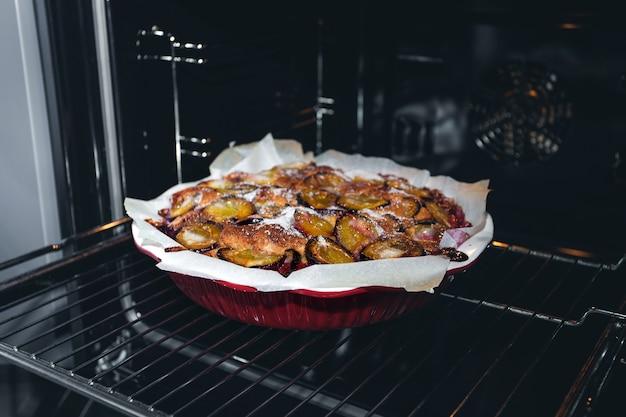 Gâteau aux prunes rustique fraîchement sorti du four à la maison dans le four de la cuisine. cuisson maison