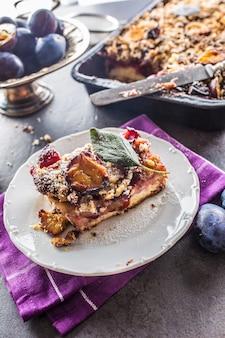 Le gâteau aux prunes sucré traditionnel sur plaque blanche.