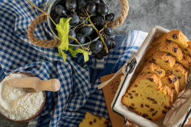 Gâteau aux raisins secs, bol de farine et raisins sur une surface en marbre