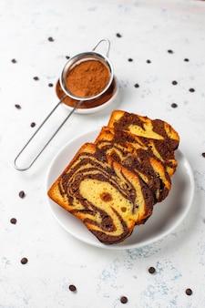 Gâteau aux raisins secs en tranches de gâteau aux raisins secs et cacao en poudre, vue du dessus