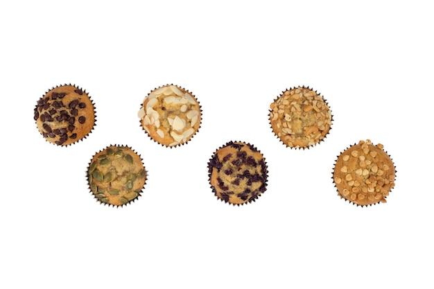 Gâteau à la banane avec une variété de garnitures, amandes, graines de citrouille, chocolat blanc foncé, cassis, noix de cajou isolées sur fond blanc avec vue de dessus.