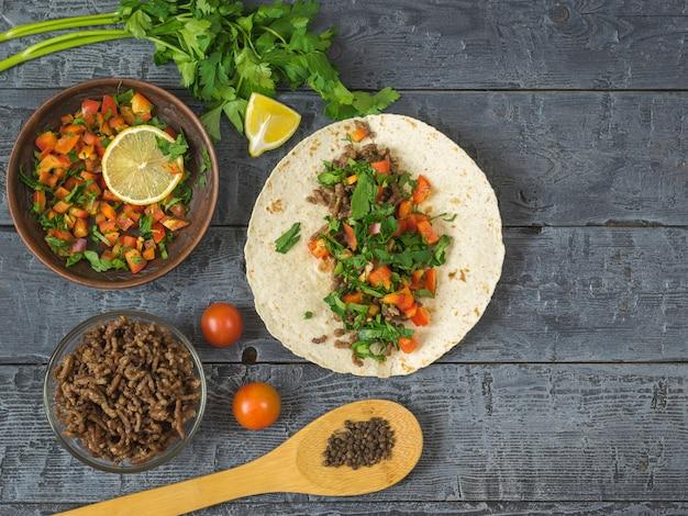 Gâteau à base de semoule de maïs avec du boeuf haché et des légumes tacos mexicains sur une table en bois