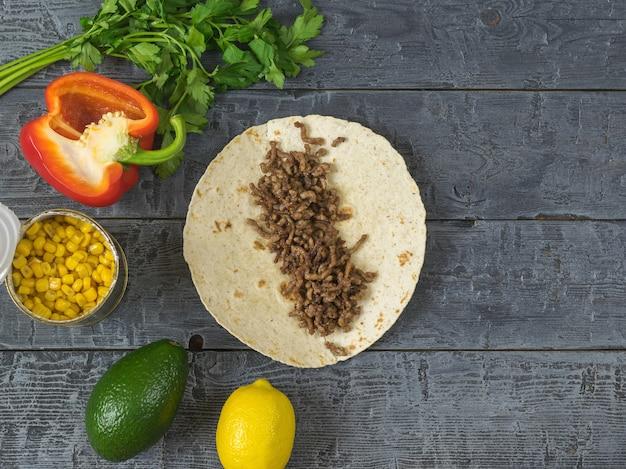 Gâteau à base de semoule de maïs avec du boeuf haché sur une table en bois et des ingrédients pour les tacos mexicains