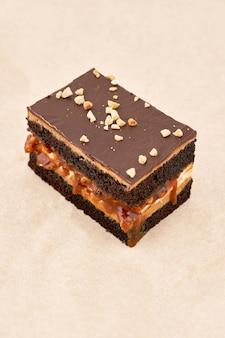 Gâteau biscuit noir avec une couche de crème et fondant au chocolat, saupoudré de noix râpées, cadre vertical