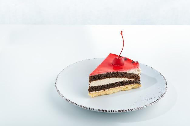 Gâteau biscuit savoureux aux cerises sur plaque blanche sur fond blanc.