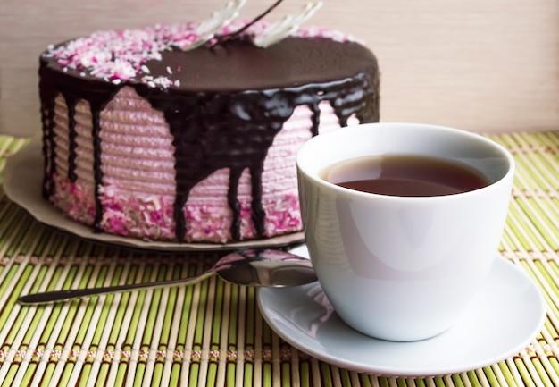 Gâteau biscuit avec soufflé aux fruits, décoré de chocolat et tasse de thé.
