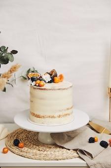 Gâteau blanc aux baies et fruits de la passion à côté d'une plante derrière un fond blanc