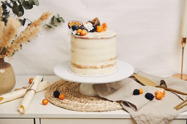 Gâteau blanc aux fruits rouges et fruits de la passion à côté d'une plante derrière un blanc