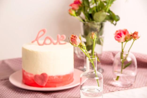 Gâteau blanc à décor rose et le mot amour au sommet parmi les petites roses blanches et roses