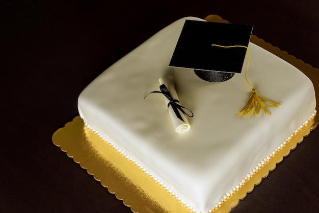 Gâteau blanc de graduation avec capuchon sur le dessus et décor de diplôme.