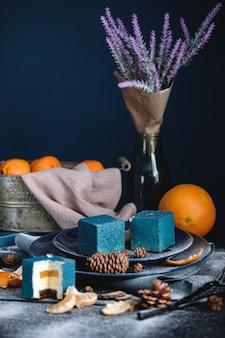 Gâteau bleu rempli d'orange et de mandarine en forme de cube. a proximité sur une table noire se trouvent des ingrédients oranges, mandarines, noix. style rustique