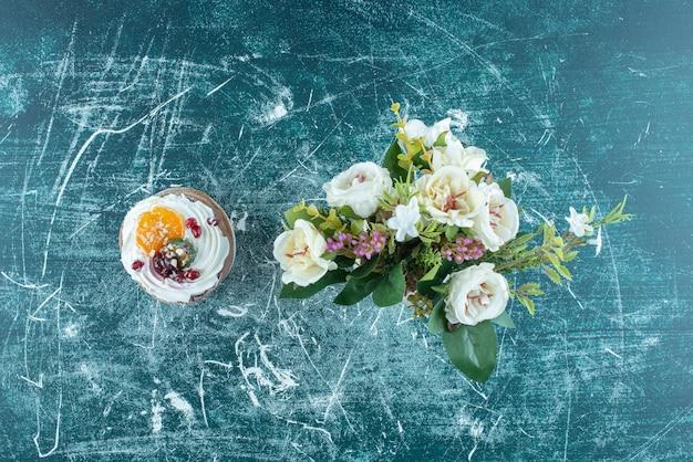 Un gâteau et un bouquet de fleurs sur fond bleu.