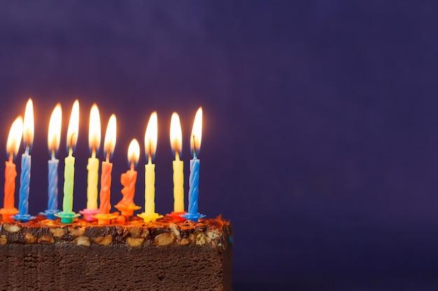 Gâteau brownie joyeux anniversaire avec des arachides, du caramel salé et des bougies allumées colorées sur le fond violet. copiez l'espace pour le texte.