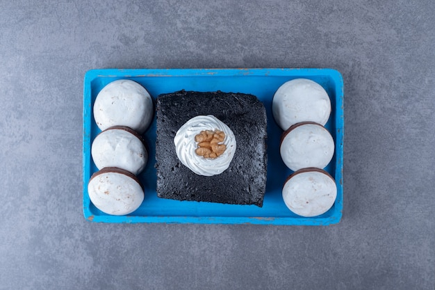 Gâteau brownie un mini gâteau pop sur une plaque en bois sur une table en marbre.