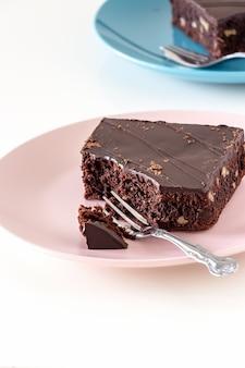 Gâteau brownie végétalien au chocolat noir fait maison avec fond clair de plaque de noix. mise au point sélective.