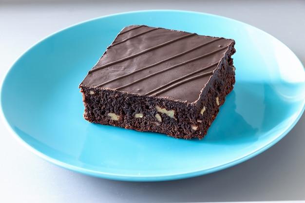 Gâteau brownie végétalien au chocolat noir fait maison avec fond clair de plaque de noix.
