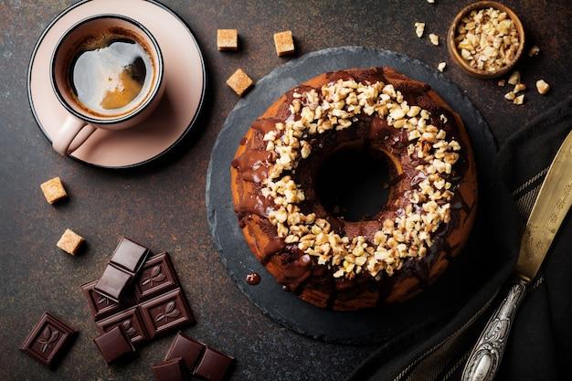 Gâteau bundt au chocolat et à la citrouille avec glaçage au chocolat et noix sur une surface en béton foncé