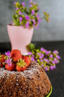 Gâteau bundt fait maison avec des fraises fraîches et des fleurs sur un tableau noir.