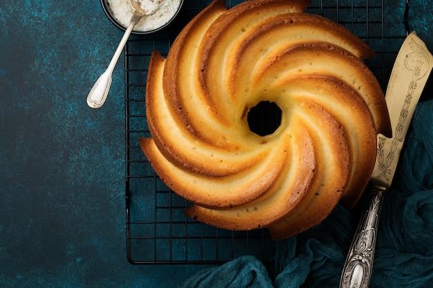 Gâteau bundt avec glaçage au sucre et noix de coco sur fond de béton ancien bleu foncé