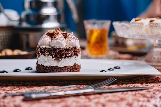 Gâteau de cacao en couches avec portion de crème blanche et morceaux de chocolat