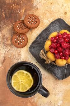 Un gâteau cadeau et des biscuits sur une assiette brune et une tasse de thé sur une table de couleurs mélangées
