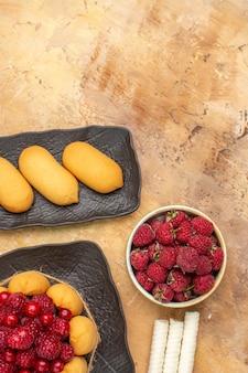 Un gâteau cadeau et des biscuits sur des assiettes brunes fruits sur table de couleurs mixtes vue verticale