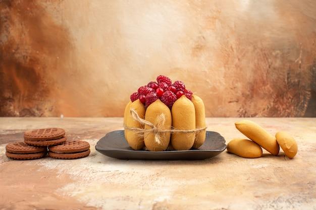 Un gâteau cadeau et des biscuits sur des assiettes brunes fruits sur table de couleurs mixtes
