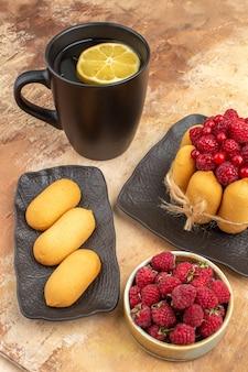 Un gâteau cadeau et du thé dans une tasse noire avec du citron et des biscuits sur table de couleurs mélangées