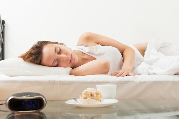 Gâteau et café en face de femme endormie