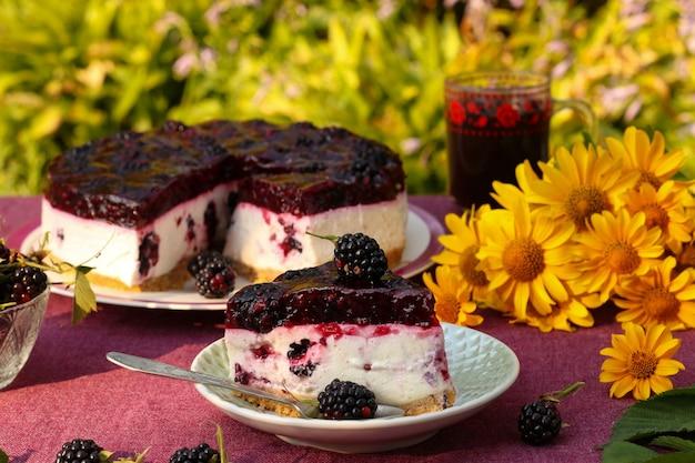 Gâteau caillé aux mûres sur une table dans le jardin contre la surface des buissons verts. nature morte