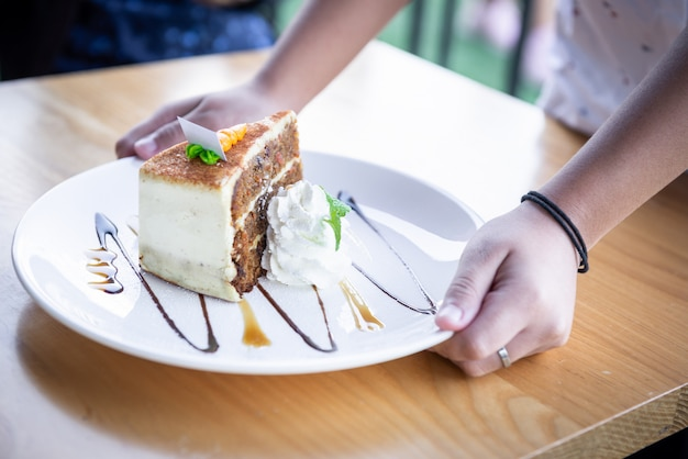 Le gâteau avec carotte est un mélange et décoré avec de la crème fouettée, du caramel, des feuilles de menthe