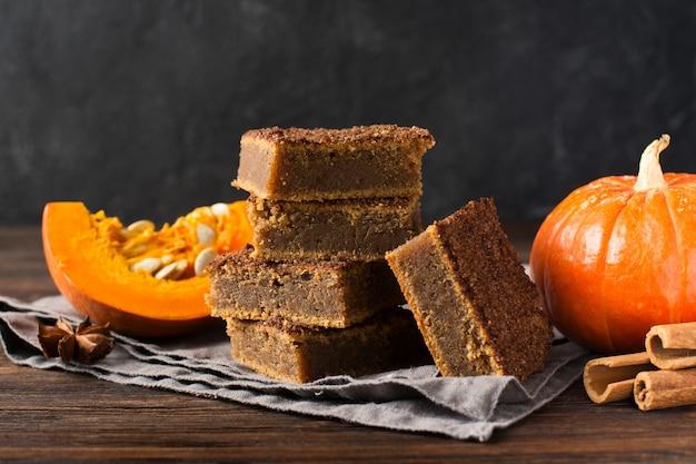 Gâteau carré de citrouilles ou pâtisserie à la cannelle et à la citrouille sur fond sombre