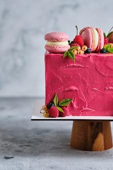 Gâteau carré rose garni de macarons et de baies fraîches. gâteau pour les vacances. le dessert est garni de framboises fraîches, de groseilles blanches, de cerises et de bleuets.