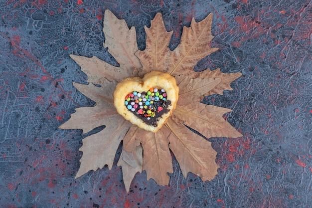 Gâteau coeur avec garniture au chocolat et bonbons.