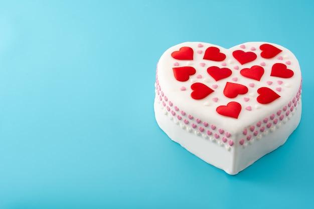 Gâteau coeur pour la saint-valentin, décoré de coeurs en sucre sur fond bleu