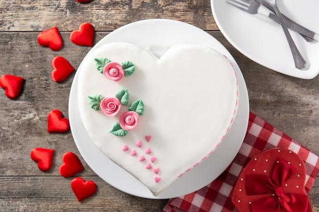 Gâteau coeur pour la saint-valentin, décoré de roses et de coeurs en sucre rose sur table en bois