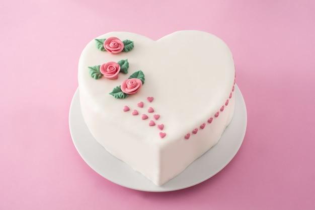 Gâteau coeur pour la saint-valentin, la fête des mères ou un anniversaire, décoré de roses et de coeurs en sucre rose sur fond rose